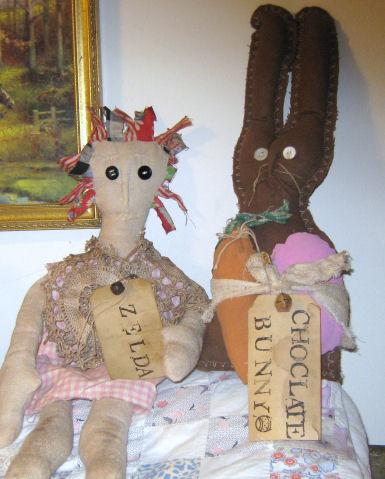 A cute handmade prim Annie doll with a giant chocolate prim bunny doll for Easter.