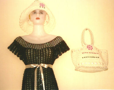 A hand-crocheted perfect little black dress and matching hat and bag for a doll.