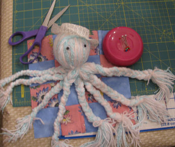 Here is Cami's easy to make yarn octopus. She made hers in pastel baby yarn colors and then made the baby quilt to go with it.