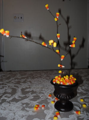 With a branch from your back yard, candy corn, a hot glue gun, and an old flower pot or urn, you can make this whimsical Candy Corn Halloween decoration.