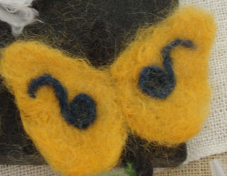 A butterfly made by dry needle felting using angora goat hair.