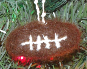 A football Christmas tree ornament made by dry needle felting with wool.