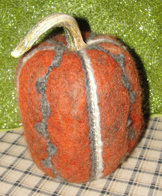 A pumpkin made by needle felting from alpaca fur.