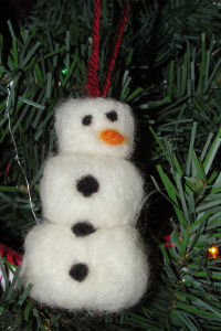 An adorable snowman tree ornament made by needle felting.