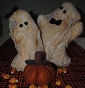 Handmade ghost couple made from quilt batting and cheesecloth were stained with coffee to look old and primitive.