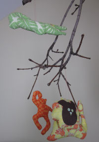 Gather a branch from your back yard and some fabric to make this adorable jungle mobile. How to make a jungle mobile from fabric and branches.
