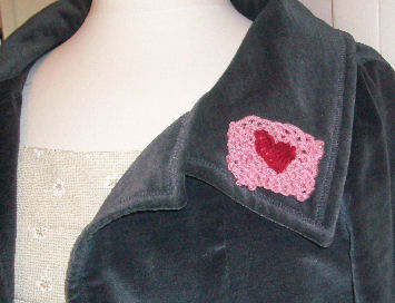 A knitted heart pin, perfect for Valentine's day.