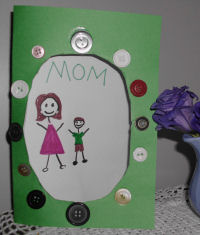 A handmade card for Mother's day, art work of a child and mom in a card for Mother's day with buttons.