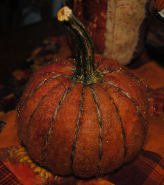 Here is a pumpkin made from orange lama fibers that were dyed. The stem is from a real pumpkin. This pumpkin was dry needle felted.