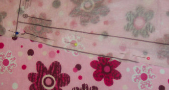 "When pinning a pattern piece onto fabric before cutting,  place pins parallel to the cutting line about 3-4"" apart."