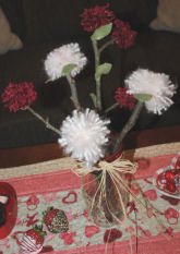 Here are some easy to make yarn pompom flowers that are glued to a tree branch stick and put in a mason jar.