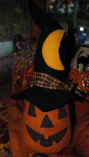 A handmade fabric pumpkin craft with a black witches hat.