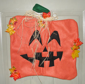 Cute Halloween pumpkin front door decoration made from felt fabric.