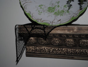A spider web doily for a Halloween decoration on a shelf.