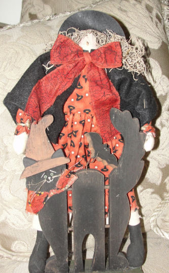 Hand sewn witch doll glued onto a painted wooden black cat figure for Halloween decorating, DIY project.